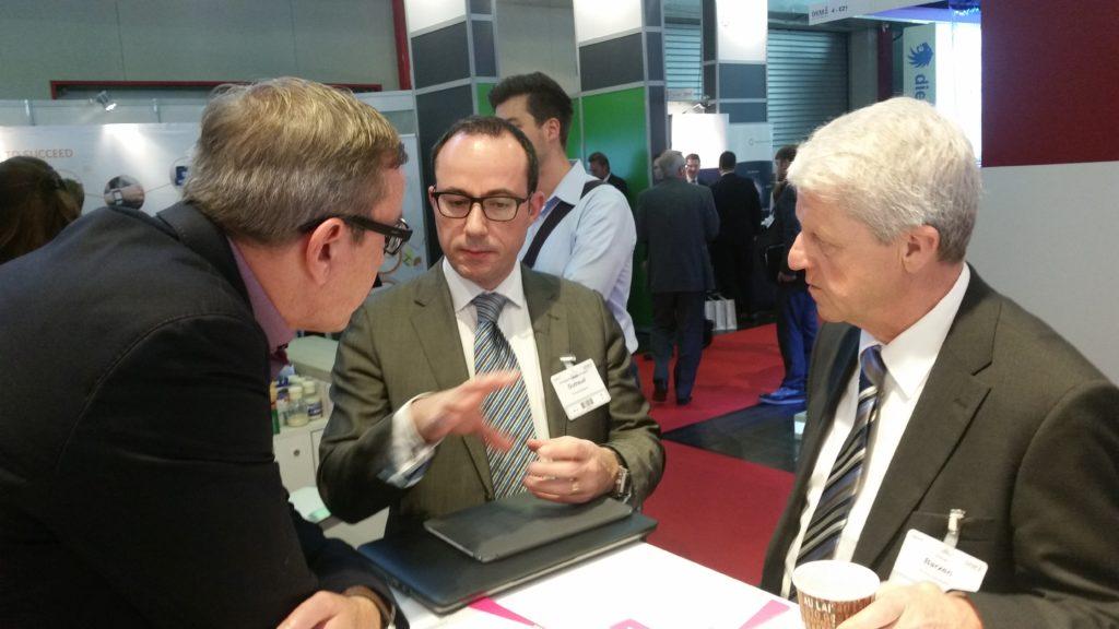 Elmar Barzen und der französische Chefentwickler von Prima Solutions im Gespräch mit Holger Koppius am Stand der Asspario AG